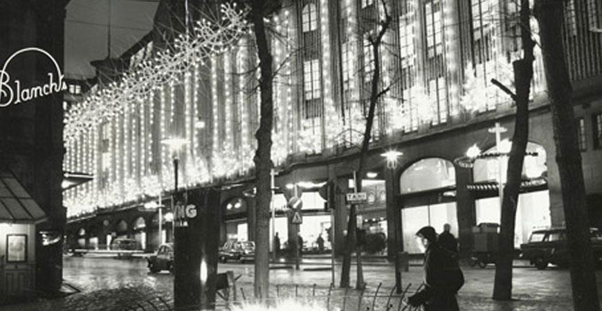 NK-huset mot Hamngatan i skymningsljus, gatubelysning och med juldekorationer. Cirka 1950–1970. NK:s historiska arkiv hos Centrum för Näringslivshistoria.